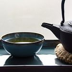 Tea_Passion_Sven-Christian Lange_Branding Photography_Ancient Black Cast Iron Kettle On Coaster Made Of Bast With Drop On Spout And Steaming Turquoise Tea Bowl On Platter