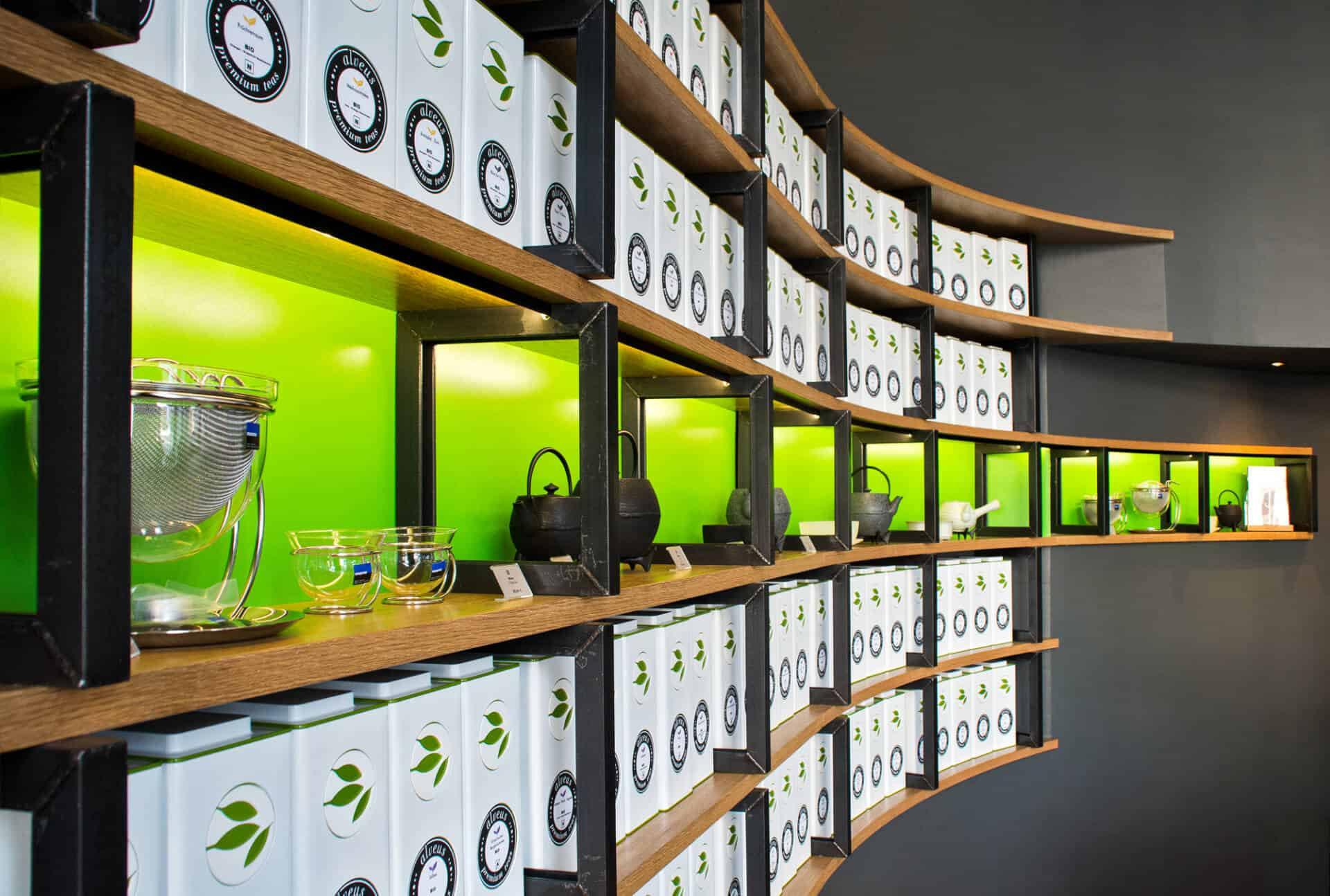 perfektes und funktionales Tee Store Konzept Retail-Design Produkt-Design Corporate-Design von Lange Architekten im ersten alveus Bio-Tee Tea-Store Alster mit Akzenten in Eichenholz und Stahl mit repräsentativer organischer Rückwand mit alveus Caddies und Logo creates-your-premium-tea in den Colonnaden Hamburg