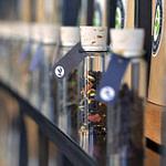 perfektes und funktionales Tee Store Konzept Retail-Design Produkt-Design Corporate-Design von Lange Architekten im ersten alveus Bio-Tee Tea-Store Alster mit Akzenten in Eichenholz und Stahl mit Tee-Regalen mit Tester-Gläsern als Tee Einkaufserlebnis in den Colonnaden Hamburg