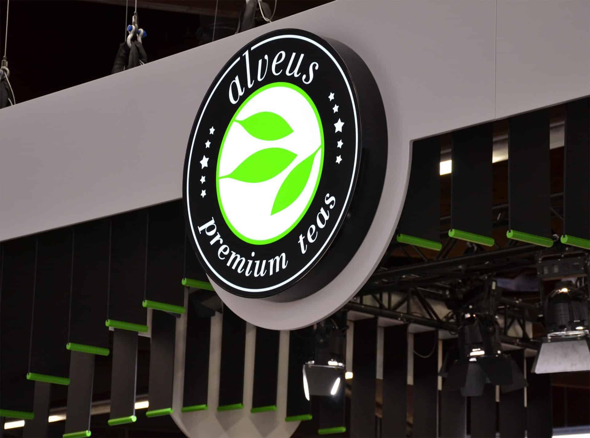 Messe-Konzept Messe-Design Corporate-Design alveus premium-teas edel in Schwarz mit Akzenten in Eiche Weiß und Grün Lamellen und Leuchtschild mit Logo an Traversen Low-Budget design von Lange Architekten für alveus Biofach
