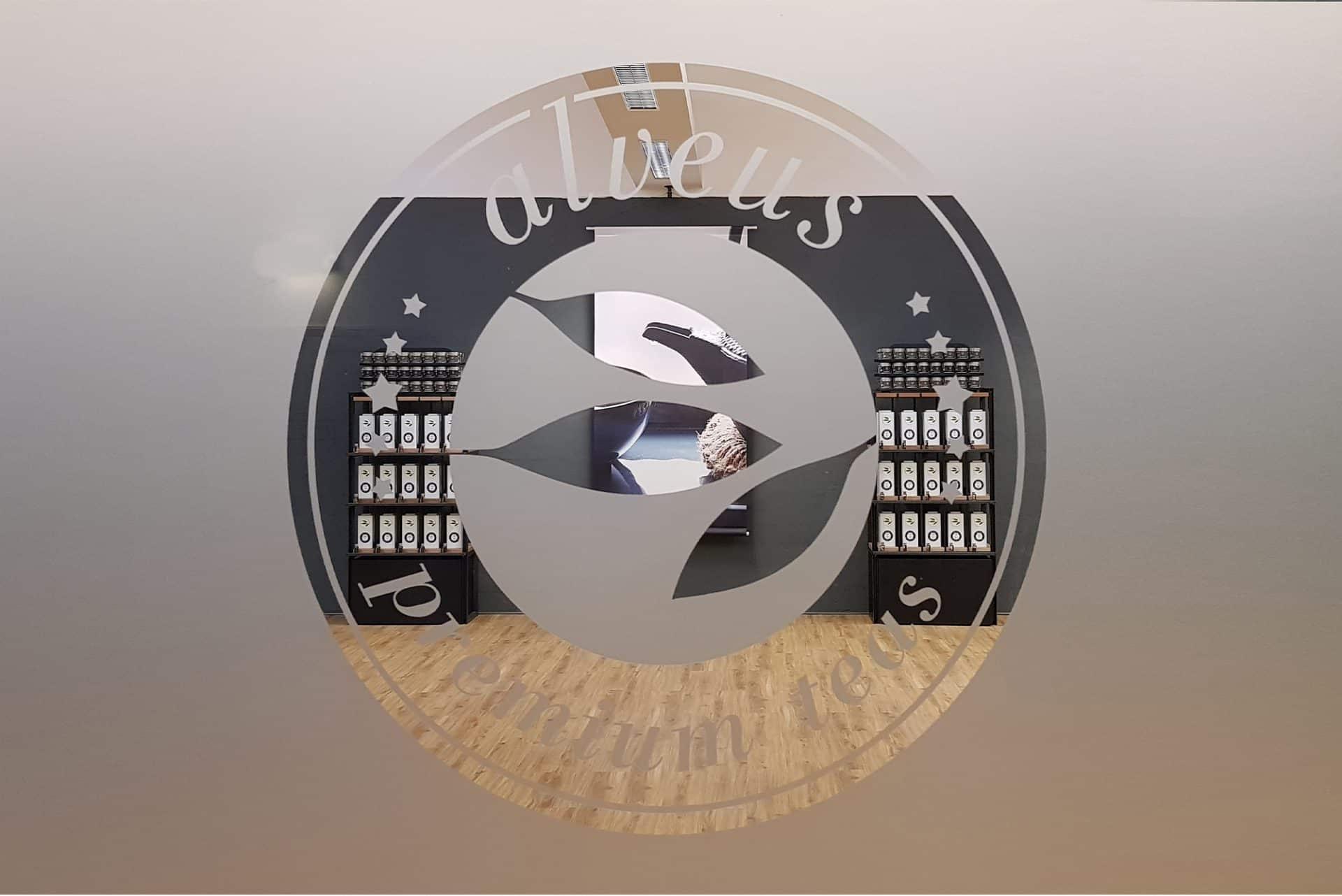 Showroom Konzept Produkt-Design Corporate-Design von Lange Architekten im zweiten Showroom von alveus premium-teas Eingang mit Glastür und Loge mit Blick für den Kunden auf Tee-Regale und Großformat-Photo-Banner von Lange Architekten