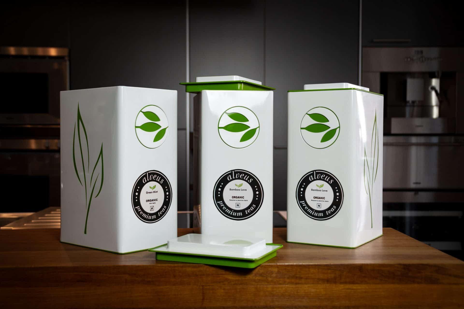 alveus premium-teas Tea-Caddy Teedose für 1 Kilo losen Tee mit Aroma-Schutz Etiketten-Lasche und individuellem runden Magnet-Etikett und Logo Relief als markantes Elementmit grünen Akzenten für alveus Tea-Stores weltweit designed und als Serienprodukt entwickelt von Lange Architekten