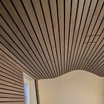 Arztpraxis-Design Empfangsbereich in der Chiropractic West von Chiropractor Corinna Haack im ästhetischen Spa Design mit geschwungenen Wänden und geschwungenen Möbeln und Produkt-Design mit dunklen Holz-Lamellen zum Wohlbefinden der Kunden
