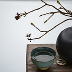 Tea Passion_Sven-Christian Lange_Branding Photography_Black Cast Iron Vase And Branch With Buds With Turquoise Matcha Bowl On Ancient Wooden Stand_Tea Ceremony_Wabi Sabi