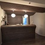 Arztpraxis-Design Empfangs-Tresen in der Chiropractic West von Chiropractor Corinna Haack im ästhetischen Spa Design mit geschwungenen Wänden und geschwungenen Möbeln und Produkt-Design mit dunklen Holz-Lamellen zum Wohlbefinden der Kunden