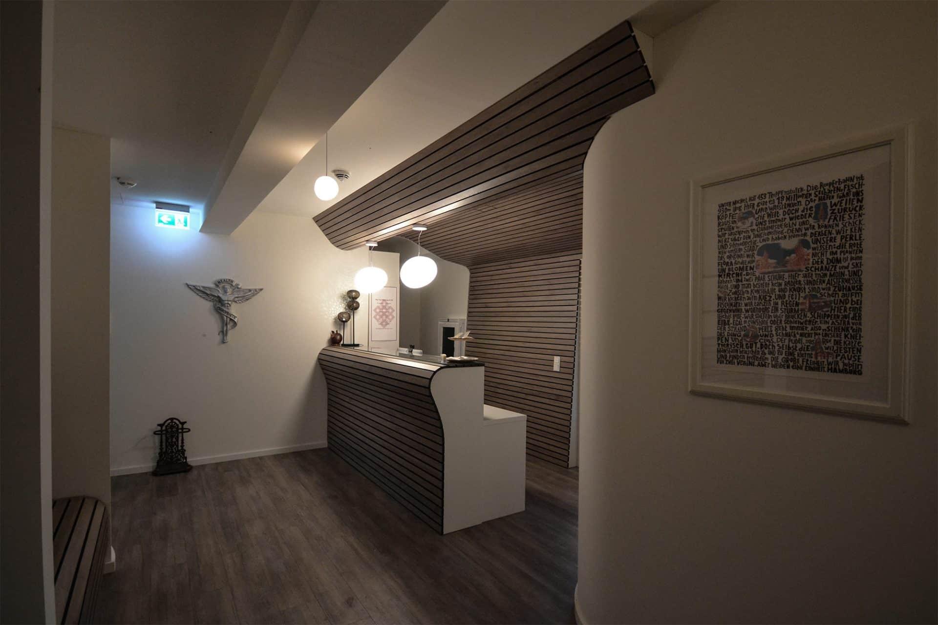 Arztpraxis-Design Empfangsbereich und Tresen in der Chiropractic West von Chiropractor Corinna Haack im ästhetischen Spa Design mit geschwungenen Wänden und geschwungenen Möbeln und Produkt-Design mit dunklen Holz-Lamellen zum Wohlbefinden der Kunden