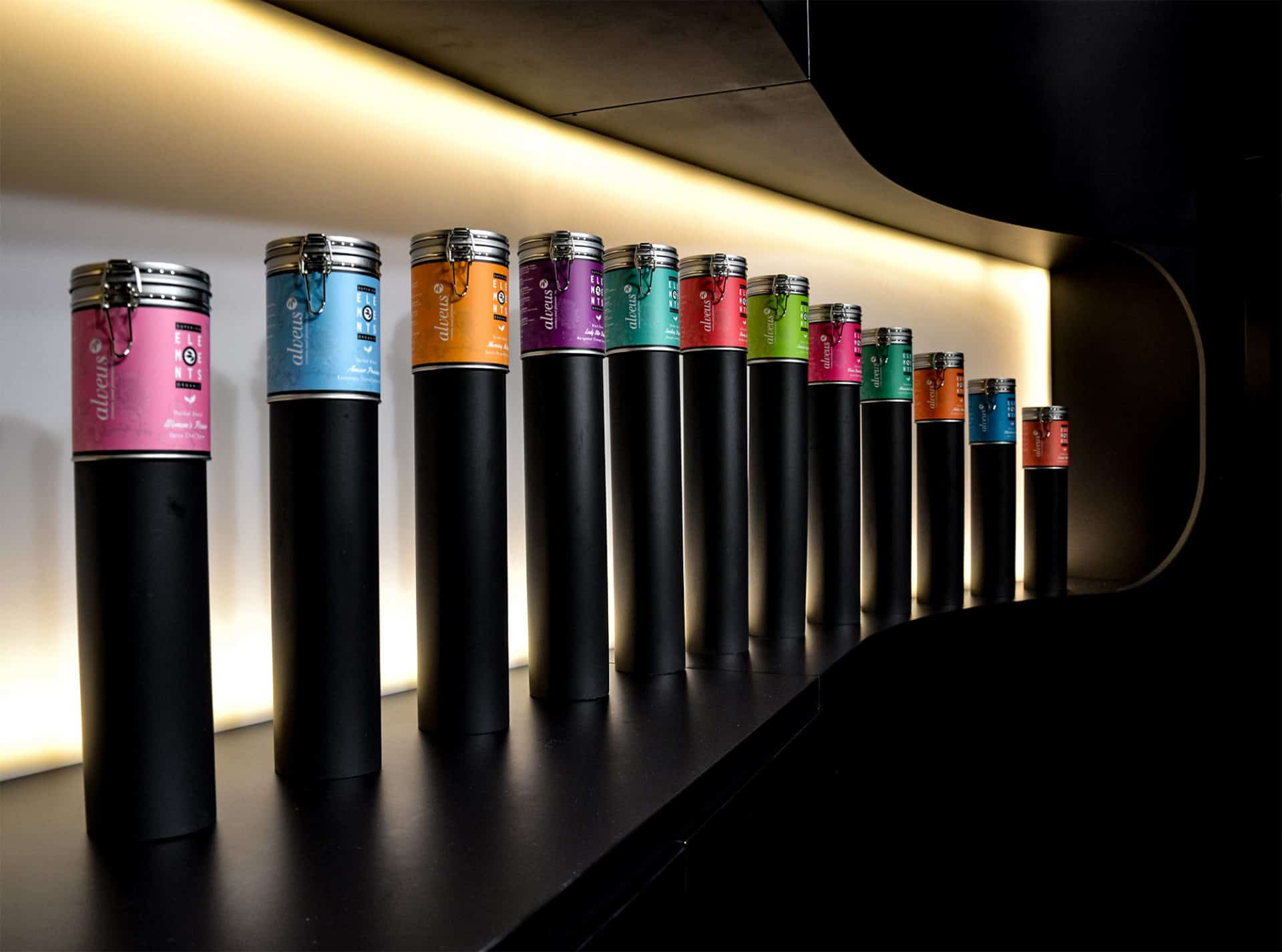 Messe-Konzept Messe-Design Corporate-Design alveus premium-teas edel in Schwarz mit Akzenten in Eiche Weiß und Grün Tee Ausschank Tresen Rückseite mit Säulen-Display für Tee-Dosen Elements Low-Budget design von Lange Architekten für alveus Biofach