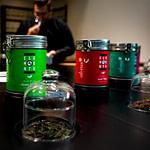 perfektes organisches und funktionales Tee Store Konzept Retail-Design Produkt-Design Corporate-Design von Lange Architekten im weißen alveus Bio-Tee Tea-Store mit Akzenten in Eichenholz und Stahl mit zentralem Probier-Tresen in der HafenCity Hamburg unweit der Elbphilharmonie